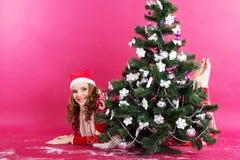 La muchacha feliz está esperando los regalos cerca de la Navidad Fotografía de archivo libre de regalías