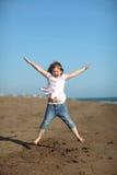 La muchacha feliz está saltando en la playa Imagen de archivo libre de regalías