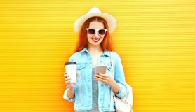 La muchacha feliz fresca que usa un smartphone sostiene la taza de café en una naranja Fotos de archivo libres de regalías