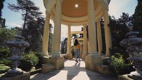 La muchacha feliz gira en de la Rotonda en un día soleado hermoso, enfocando de la cámara metrajes