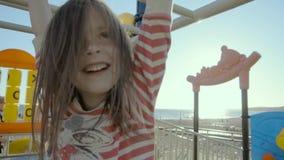 La muchacha feliz guarda las barras del entrenamiento de la calle sobre ella y sonríe en una orilla de mar en el slo-MES metrajes
