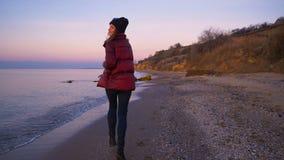 La muchacha feliz hermosa corre a lo largo de la playa a la puesta del sol del otoño en la cámara lenta frío almacen de video