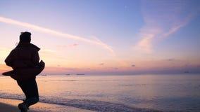 La muchacha feliz hermosa corre a lo largo de la playa a la puesta del sol del otoño en la cámara lenta frío almacen de metraje de vídeo
