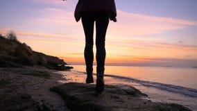 La muchacha feliz hermosa corre a lo largo de la playa a la puesta del sol del otoño en la cámara lenta frío metrajes