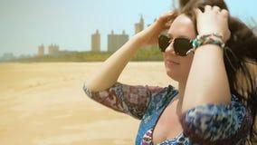 La muchacha feliz hermosa en vidrios se sienta en la playa en un día de verano soleado Ciérrese encima de tiro Cámara lenta almacen de video