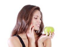 La muchacha feliz hermosa mira la manzana verde Imagenes de archivo