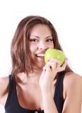 La muchacha feliz hermosa muerde la manzana verde fresca Fotografía de archivo libre de regalías