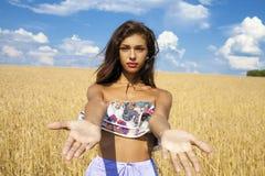 La muchacha feliz joven atractiva lleva a cabo las manos en un campo de trigo Fotografía de archivo libre de regalías