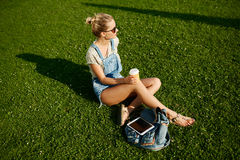 La muchacha feliz joven bebe la sentada al aire libre del café en hierba fotos de archivo libres de regalías