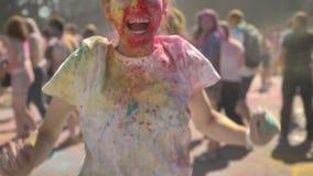 La muchacha feliz joven en polvo colorido es de salto y de griterío en festival del holi en d3ia en el verano, concepto del color metrajes