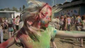 La muchacha feliz joven en polvo colorido es de salto y de sacudida de la cabeza en festival del holi en d3ia en el verano, conce metrajes