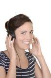 La muchacha feliz joven escucha la música con los auriculares Imagen de archivo