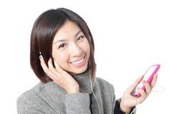 La muchacha feliz joven escucha música con los auriculares Imagen de archivo libre de regalías