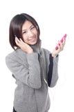 La muchacha feliz joven escucha música con los auriculares Fotos de archivo