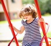 La muchacha feliz joven está balanceando en patio Foto de archivo