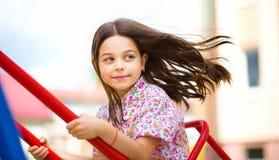 La muchacha feliz joven está balanceando en patio Imagenes de archivo