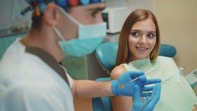 La muchacha feliz joven está en gabinete dental en el tratamiento y consultating metrajes