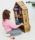La muchacha feliz juega con la casa de muñecas de la cartulina El niño precioso divertido se está divirtiendo fotografía de archivo