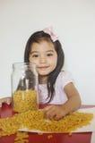 La muchacha feliz juega los macarrones imagenes de archivo