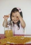 La muchacha feliz juega los macarrones imagen de archivo