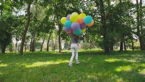 La muchacha feliz, juguetona presenta con los globos coloridos en el paseo en parque soleado almacen de video