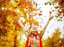 La muchacha feliz lanza para arriba las hojas de otoño en el parque para el paseo al aire libre Fotografía de archivo