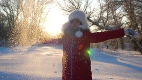 La muchacha feliz lanza para arriba nieve con sus manos en la puesta del sol en caídas de la nieve del bosque y las chispas en so almacen de video