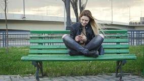 La muchacha feliz linda con el pelo rubio largo en la chaqueta de cuero endereza el artilugio del uso que se sienta en el banco e Fotografía de archivo