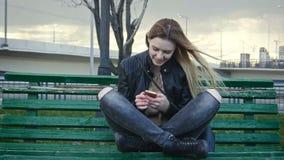 La muchacha feliz linda con el pelo rubio largo en la chaqueta de cuero endereza el artilugio del uso que se sienta en el banco e Imagen de archivo