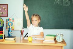 La muchacha feliz linda de los alumnos aumentó las manos en clase imagen de archivo libre de regalías