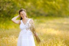 La muchacha feliz linda está en el campo, recolectando el trigo Fotos de archivo libres de regalías