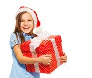 La muchacha feliz lleva el regalo de Navidad en el sombrero de Papá Noel Imágenes de archivo libres de regalías