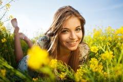 La muchacha feliz miente entre wildflowers amarillos Fotografía de archivo