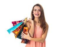 La muchacha feliz mira la derecha y los controles en el suyo dan muchos paquetes grandes se aíslan del fondo blanco Fotografía de archivo libre de regalías