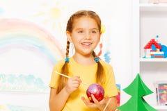 La muchacha feliz pinta la bola del Año Nuevo para el árbol de navidad Imagen de archivo
