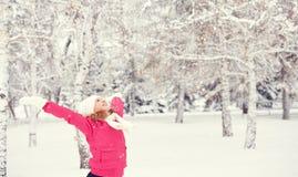 La muchacha feliz que disfruta de vida y los tiros nievan en el invierno al aire libre Foto de archivo