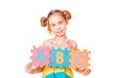 La muchacha feliz que lleva a cabo alfabeto pone letras a ABC Fotografía de archivo