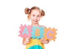 La muchacha feliz que lleva a cabo alfabeto pone letras a ABC Imagen de archivo libre de regalías