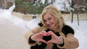 La muchacha feliz que muestra el corazón firma adentro el parque del invierno almacen de metraje de vídeo