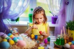 La muchacha feliz que pinta los huevos de Pascua, pequeño niño en casa se divierte Día de fiesta de la primavera imágenes de archivo libres de regalías