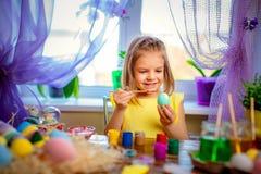 La muchacha feliz que pinta los huevos de Pascua, pequeño niño en casa se divierte Día de fiesta de la primavera fotos de archivo libres de regalías
