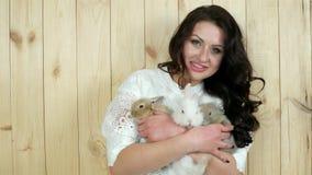 La muchacha feliz que sostiene los conejos en sus brazos, protección de animales, mujer joven ama las liebres nacionales minúscul almacen de metraje de vídeo