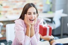 La muchacha feliz que trabajaba en la oficina recibió un regalo imagen de archivo libre de regalías