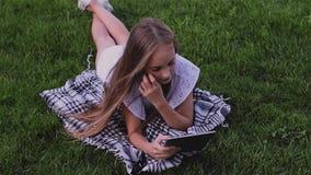 La muchacha feliz que usa la PC de la tableta miente en hierba en el parque metrajes