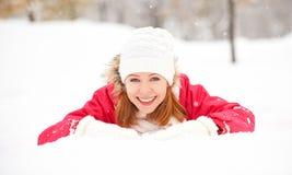 La muchacha feliz ríe mientras que miente en la nieve en invierno al aire libre Imágenes de archivo libres de regalías