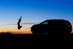 La muchacha feliz salta cerca de SUV Fotos de archivo