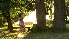 La muchacha feliz salta en parque en luz de la puesta del sol Tiro de la c?mara lenta almacen de metraje de vídeo