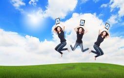 La muchacha feliz salta la PC de la tablilla de la demostración con el cielo Imagen de archivo libre de regalías