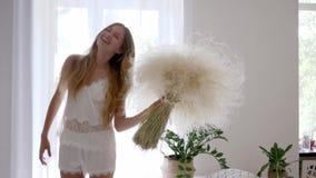 La muchacha feliz sana en pijama salta con el ramo de hierbas de la pluma en el sitio acogedor, alergia libre almacen de metraje de vídeo