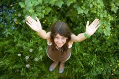 La muchacha feliz se coloca en una hierba verde Foto de archivo libre de regalías